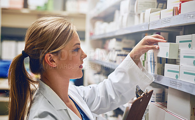 Buy stock photo Shot of a pharmacist looking at medication on a shelf