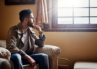 Buy stock photo Shot of a handsome young man deep in thought while sitting on a chair at home
