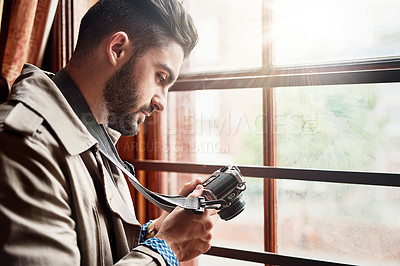Buy stock photo Shot of a handsome young man standing by a window at home looking at his camera