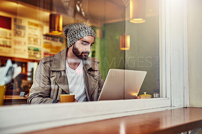 Buy stock photo Shot of a handsome young man sitting at a cafe counter using a laptop