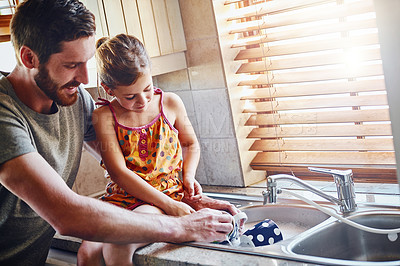 Buy stock photo Cropped shot of a father and his little daughter washing dishes together at home