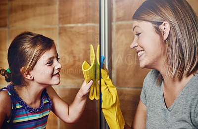 Buy stock photo Cropped shot of a mother and her little daughter cleaning a bathroom together at home