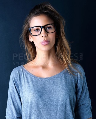 Buy stock photo Studio portrait of a cute teenage girl in glasses sticking out her tongue posing against a dark background