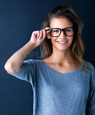 Buy stock photo Studio portrait of a cute teenage girl in glasses posing against a dark background