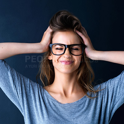 Buy stock photo Studio shot of a cute teenage girl in glasses with her hands in her hair posing against a dark background