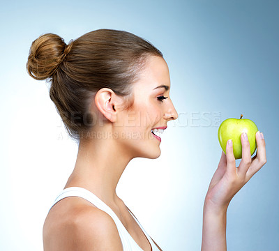 Buy stock photo Shot of a health-conscious young woman posing with an apple in studio