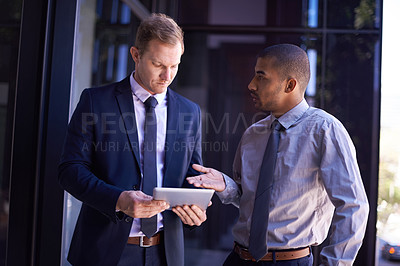 Buy stock photo Shot of two colleagues using a digital tablet together at work