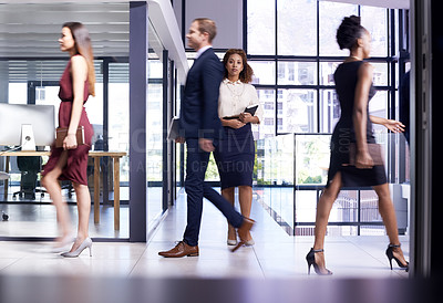 Buy stock photo Shot of businesspeople walking in a busy office