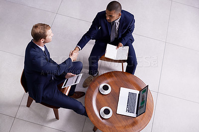 Buy stock photo High angle shot of two businessmen shaking hands during a meeting in an office