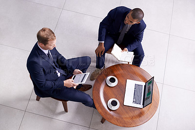 Buy stock photo High angle shot of two businessmen having a discussion in an office