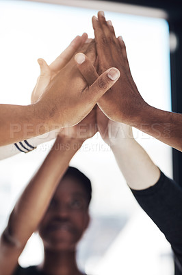 Buy stock photo Cropped shot of a group of colleagues giving each other a high five at work