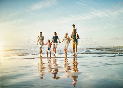 Buy stock photo Shot of a happy multi-generational family walking on the beach together