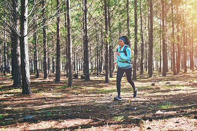 Buy stock photo Full length shot of an athletic young woman out for a jog in the woods