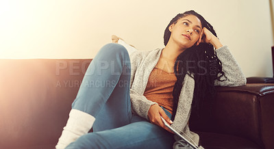 Buy stock photo Shot of a young woman contemplating while relaxing at home with her tablet