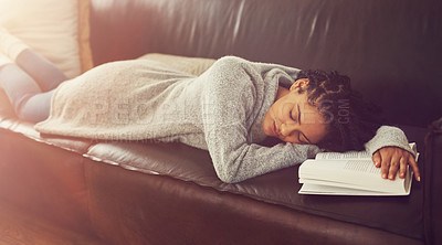 Buy stock photo Shot of a young woman asleep on her couch with a book in front of her