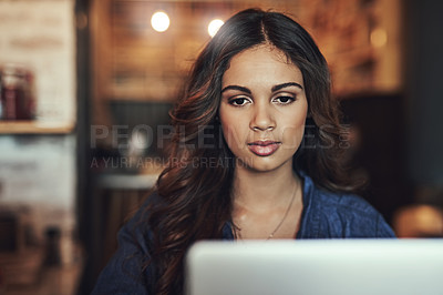 Buy stock photo Shot of a relaxed young woman using her laptop in a coffee shop
