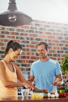 Buy stock photo Shot of a relaxed couple cooking together in their kitchen at home
