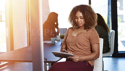 Buy stock photo Shot of a businesswoman using a digital tablet with her colleagues blurred in the background