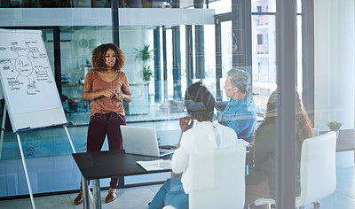 Buy stock photo Shot of a businesswoman delivering a presentation to her colleagues in a boardroom meeting
