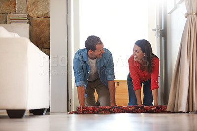Buy stock photo Shot of a mature couple rolling out a carpet together at home