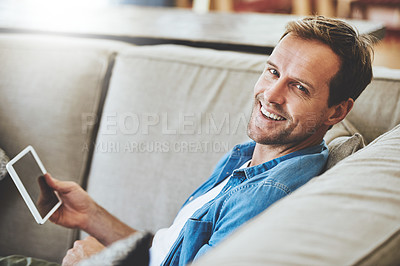 Buy stock photo High angle portrait of a man using his tablet while sitting on the sofa at home