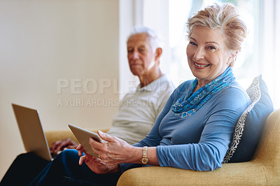 Buy stock photo Portrait of a senior woman using a digital tablet while her husband uses a laptop on the sofa at home