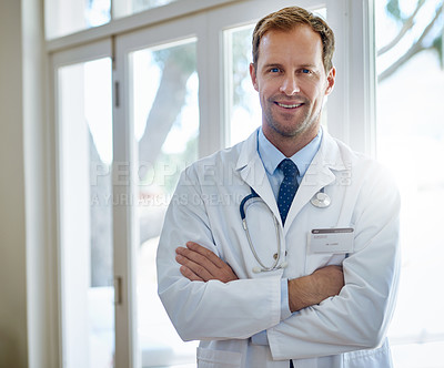 Buy stock photo Portrait of a smiling male doctor standing with his arms crossed in a hospital