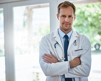 Buy stock photo Portrait of a male doctor standing with his arms crossed in a hospital