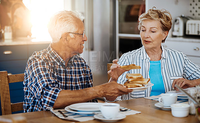 Buy stock photo Cropped shot of a senior couple having breakfast together at home