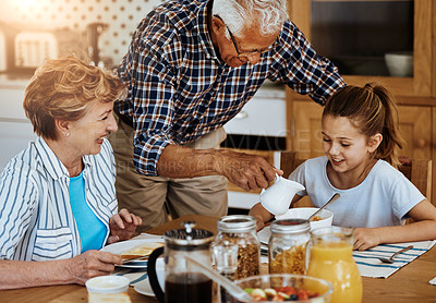 Buy stock photo Cropped shot of a little girl having breakfast with her grandparents at home