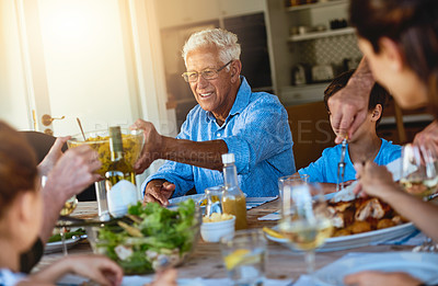 Buy stock photo Shot of a happy family enjoying lunch together around a table outside