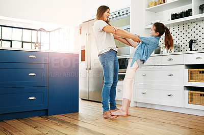 Buy stock photo Shot of a happy mother and daughter playfully dancing together at home