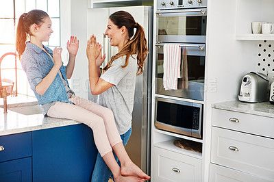 Buy stock photo Shot of a happy mother and daughter playing a clapping game at home