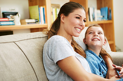 Buy stock photo Shot of a happy mother and daughter relaxing together on the sofa at home