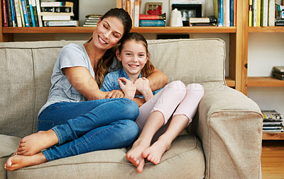 Buy stock photo Portrait of a happy mother and daughter relaxing together on the sofa at home