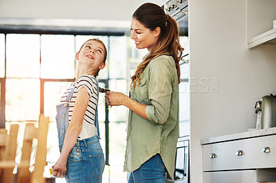 Buy stock photo Shot of a happy mother braiding her daughter's hair at home