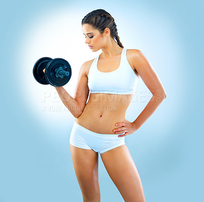 Buy stock photo Studio shot of an attractive young woman working out with a dumbbell against a blue background