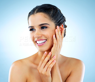 Buy stock photo Studio shot of a beautiful young woman with gorgeous skin posing against a blue background