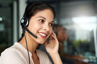 Buy stock photo Cropped shot of a call centre agent working in an office with her colleagues in the background