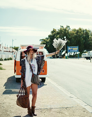 Buy stock photo Shot of a young hipster woman hitchhiking at the side of the road with her broken down van in the background