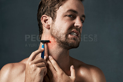Buy stock photo Cropped shot of a handsome young man grimacing while shaving