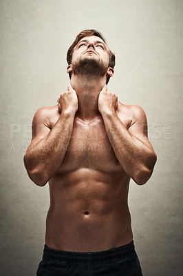 Buy stock photo Shot of a handsome and muscular young man posing shirtless in the studio