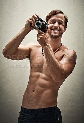 Buy stock photo Studio shot of a shirtless young man taking photos with a vintage camera