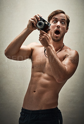 Buy stock photo Studio shot of a shirtless young man taking photos with a vintage camera and looking amazed
