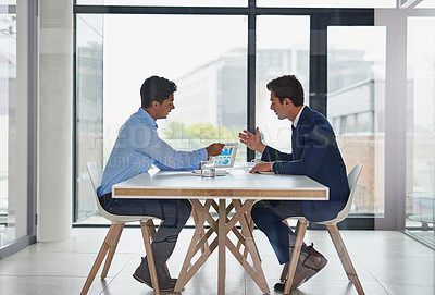Buy stock photo Shot of two businessmen using a digital tablet during a meeting in an office