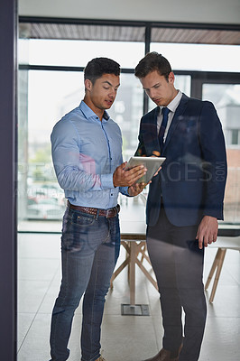 Buy stock photo Shot of two businessmen discussing something on a digital tablet in an office