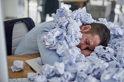 Buy stock photo Shot of a young businessman surrounded by piles of paper in an office