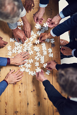 Buy stock photo High angle shot of a group of businesspeople building a puzzle together in an office