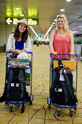 Buy stock photo Shot of two young friends pushing suitcases in trollys while walking together through an airport