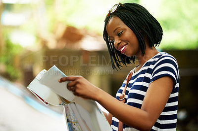 Buy stock photo Shot of a smiling young woman reading a map while traveling in Thailand
